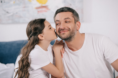 happy daughter kissing cheek of cheerful father in bedroom