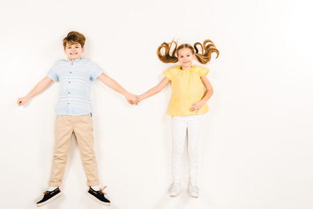 top view of cheerful kids holding hands and smiling on white
