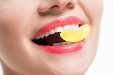 cropped view of smiling girl eating yellow jelly candy isolated on white