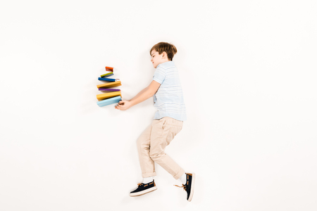top view of cute kid holding colorful books on white Stock Photo - 122824722