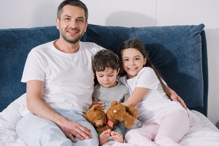 cheerful father sitting on bed with happy daughter and sad toddler son