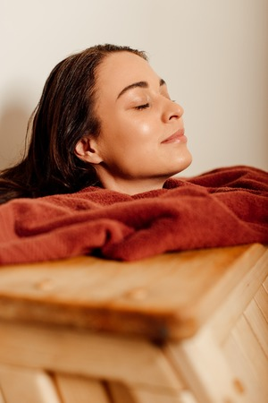 smiling woman taking steam bath with closed eyes in spa center