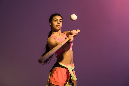 attractive sportive african american girl playing baseball on purple background Stok Fotoğraf