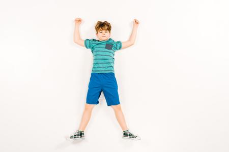 Vista superior del niño lindo con las manos por encima de la cabeza mirando a la cámara en blanco Foto de archivo