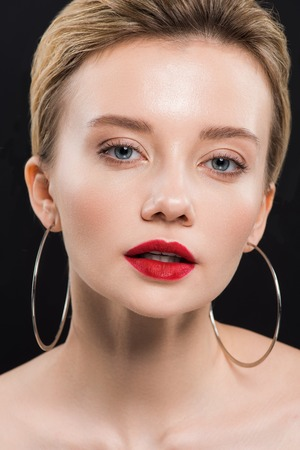 pretty young woman in earrings looking at camera isolated on black Stock Photo