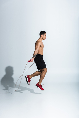 side view of mixed race man in black shorts and red sneakers jumping with skipping rope on white