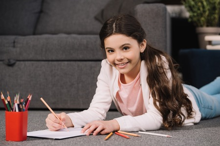 cheerful kid lying on floor and drawing on paper in living room