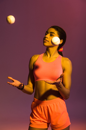 smiling african american girl in pink sports bra and shorts juggle with balls on purple background Stockfoto