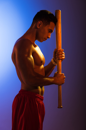 handsome mixed race man with muscular torso holding baseball bat on blue and dark purple gradient background Stockfoto - 122827689