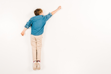 top view of kid lying and gesturing on white