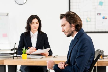 El enfoque selectivo de un hombre guapo sentado cerca de un atractivo reclutador en la oficina Foto de archivo