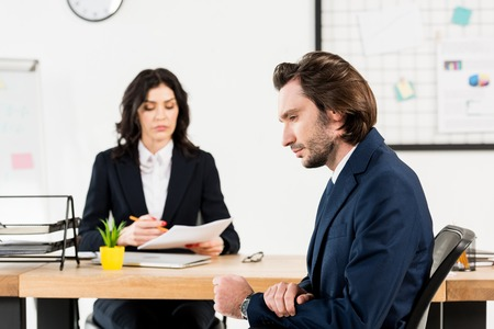 Selektiver Fokus eines gutaussehenden Mannes, der in der Nähe eines attraktiven Personalvermittlers im Büro sitzt Standard-Bild