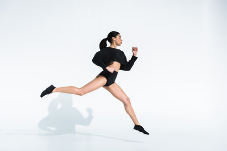 side view of sportive african american girl in black sportswear and sneakers running on white