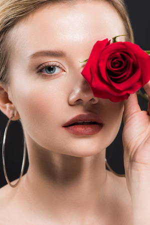 selective focus of attractive young woman holding red rose isolated on black