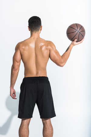 back view of athletic man in black shorts holding brown ball on white