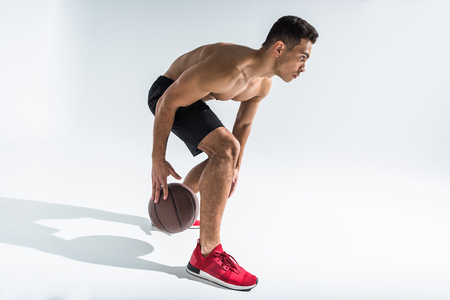 handsome mixed race man in red sneakers playing ball on white background Stock Photo