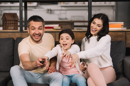 happy man holding remote controller near daughter and wife at home