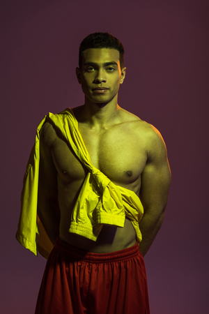 sportive mixed race man with muscular torso looking at camera on dark background Stock Photo