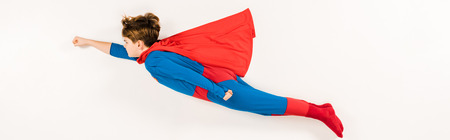 panoramic shot of adorable kid in super hero costume flying on white Foto de archivo
