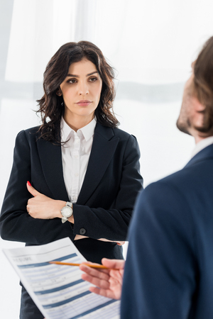 selective focus of attractive woman standing with crossed arms near man with resume 免版税图像
