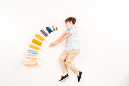 top view of surprised kid near colorful books on white