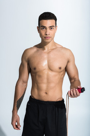 handsome mixed race man with muscular torso holding jump rope and looking at camera on white