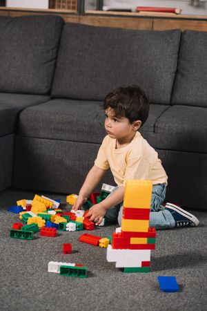 selective focus of cute toddler playing with colorful toy blocks in living room Banque d'images - 122853701