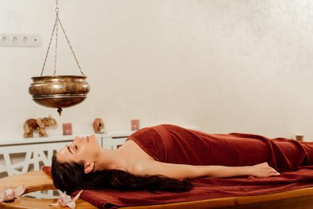 vista laterale della donna sdraiata sotto la nave shirodhara durante la procedura ayurvedica Archivio Fotografico
