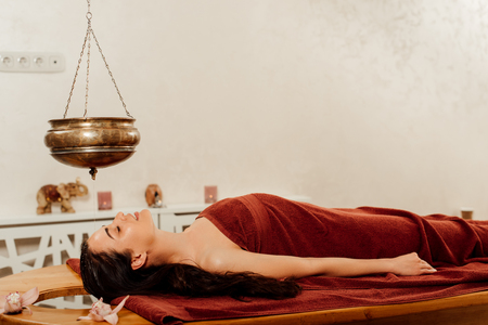 Vue latérale d'une femme allongée sous le vaisseau shirodhara pendant la procédure ayurvédique Banque d'images