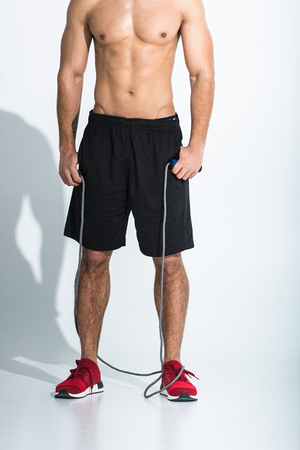 partial view of man in black shorts and red sneakers holding jump rope on white