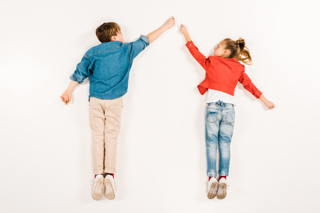 top view of cute kids gesturing while lying on white