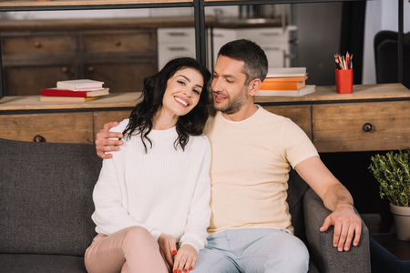 happy man hugging cheerful wife while sitting on sofa at home