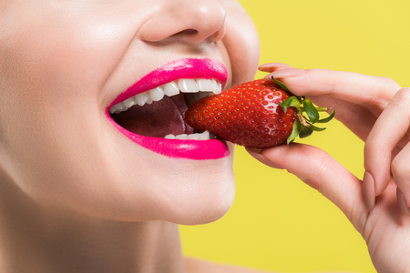 cropped view of happy woman eating tasty strawberry isolated on yellow