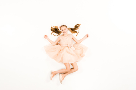 top view of happy child looking at camera while flying on white