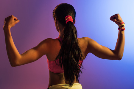 back view of athletic african american girl on purple and blue gradient background