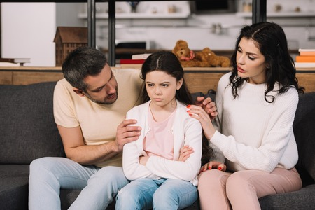 worried parents touching offended daughter sitting on sofa with crossed arms 版權商用圖片