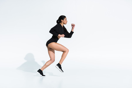 side view of beautiful sportive african american girl in black sportswear running on white