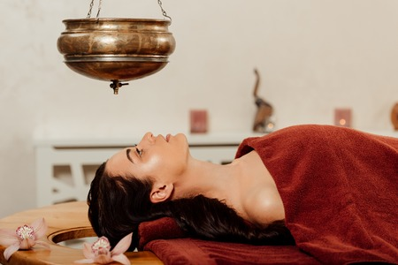 side view of woman lying under shirodhara vessel during ayurvedic procedure