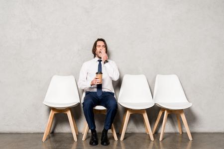 bel homme fatigué bâillant tout en tenant un gobelet en papier et assis sur une chaise