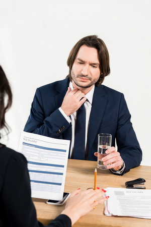 selective focus of handsome man holding glass of water near recruiter in office Imagens