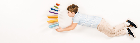 panoramic shot of cute kid holding colorful books while flying on white
