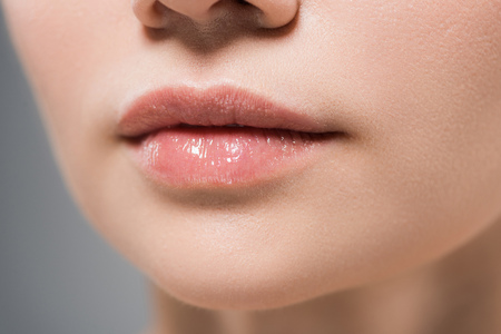 cropped view of woman with soft lips isolated on grey