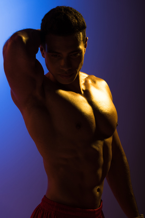 good-looking mixed race man with muscular torso posing at camera on blue and dark purple gradient background Stock Photo