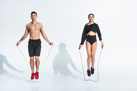 sportive multicultural woman and man jumping with skipping ropes on white