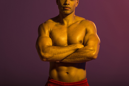 cropped view of athletic man posing at camera with crossed arms on purple background Stock Photo