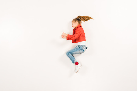 top view of cheerful kid in blue jeans gesturing on white 版權商用圖片