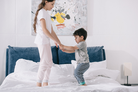 happy child holding hands with adorable toddler brother while standing on bed Stockfoto