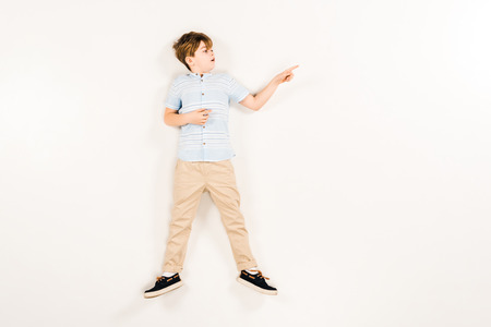 top view of surprised kid pointing with finger while lying on white
