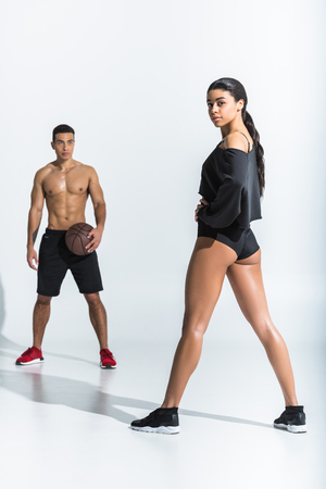 mixed race man with ball looking at attractive sportive african american girl on white
