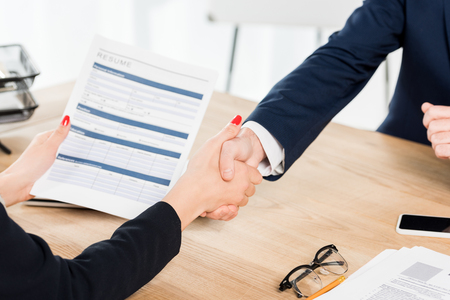 cropped view of recruiter holding resume and shaking hands with employee in office